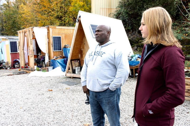 TRIBUNE PHOTO: LYNDSEY HEWITT - Terrance Moses, left, has been helping to weatherize the pods for winter. Bernadette Stetz, right, is one of the site managers for Catholic Charities who works at the village.