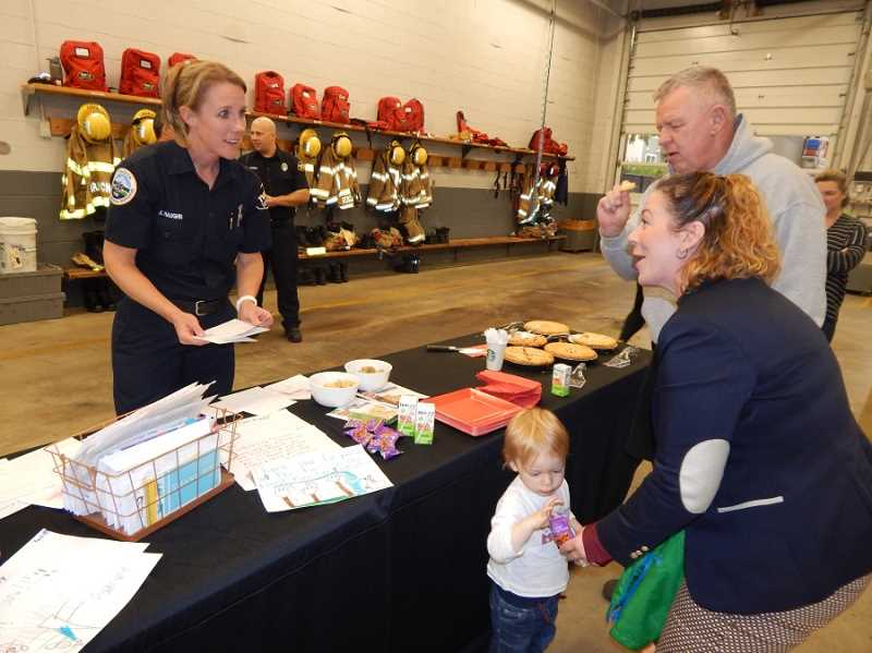 BARBARA SHERMAN - TVF&R Public Affairs Officer Kim Haughn (left) looks through all the thank you cars and letters to firefighters while talking to Jaimie Fender and her dad Bob Ellis in the Station 35 engine bay.