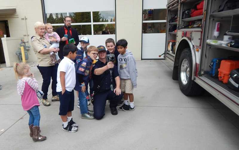 BARBARA SHERMAN - TVF&R firefighter Matt Fehrenbacher shows Cub Scouts and friends one of the cool pieces of technology carried on Engine 35, just one of many pieces of equipment firefighters have at their disposal.