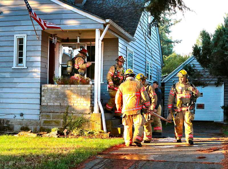 DAVID F. ASHTON - After putting out the small electrical fire in this house, some firefighters departed while others headed back inside to make sure all embers had been extinguished.