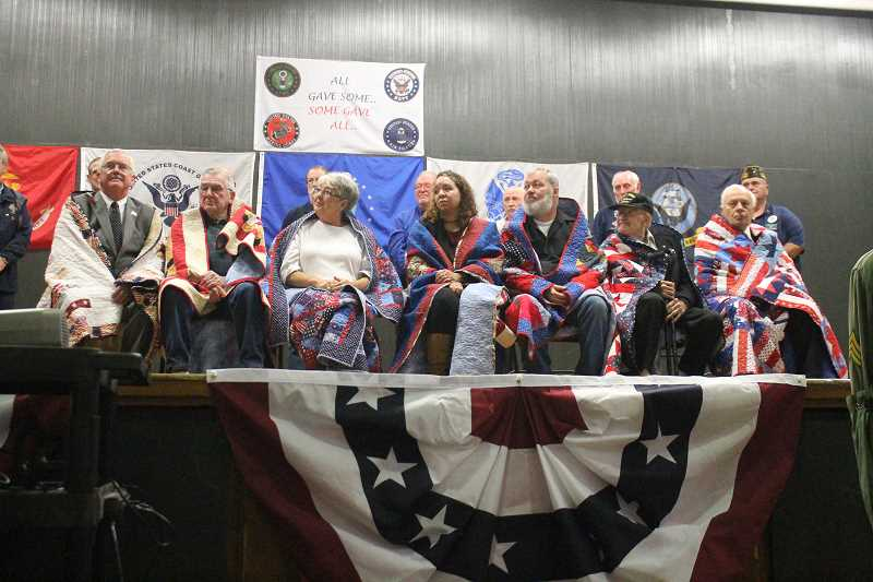 PIONEER PHOTO: CONNER WILLIAMS - Local veterans receive their Quilts of Valor during the 2017 Veterans Day Program at MRMS on Nov. 8. From left to right: Mike Clarke, Richard Clarke, Janet Williams (on behalf of her late husband Tim Williams), Tamika Phillips, Stephen R. Phillips, Gerald George and William Blackburn.