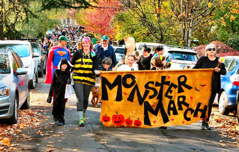 DAVID F. ASHTON - Having won the right to carry the Monster March banner, at the annual Llewellyn Foundation auction, the Wright family sets off east on S.E. Tolman Street from the school, heading for Milwaukie Avenue.