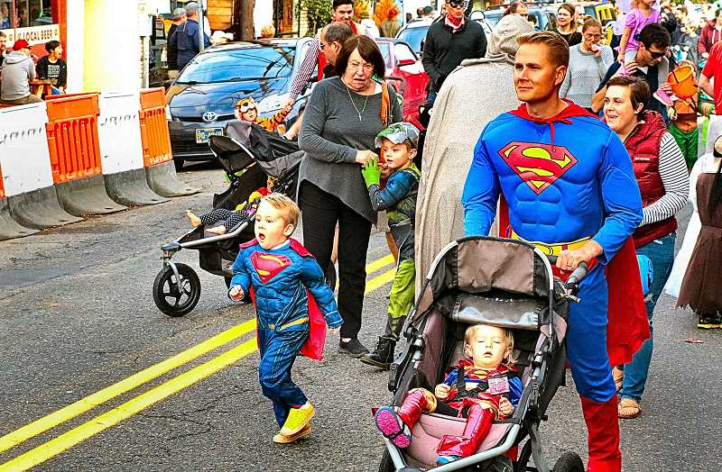 DAVID F. ASHTON - The Rasmussen Superfamily of young Atticus - who marches next to his dad Kyle, who pushes Wren in a stroller - stroll the parade.