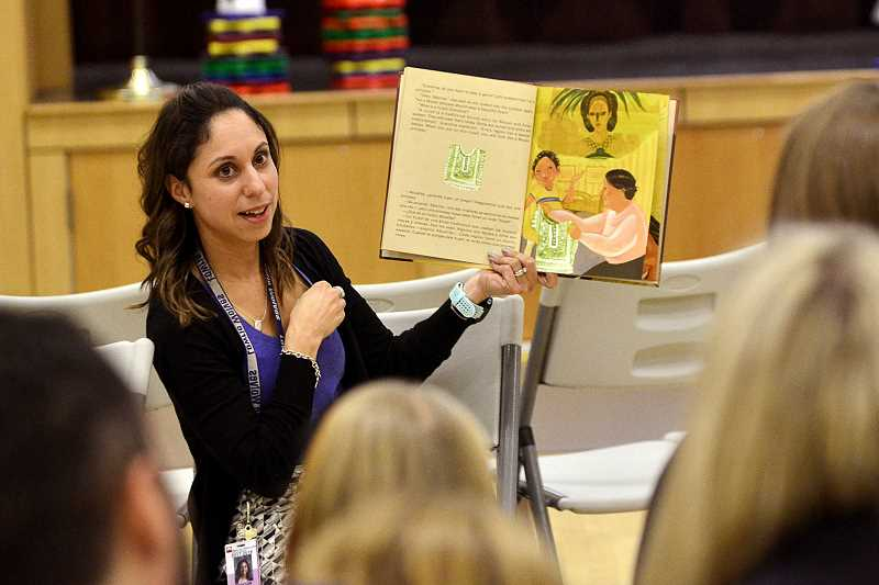 SPOKESMAN PHOTO: VERN UYETAKE - Elissa Lee reads a story to families during the Nov. 9 Dual Language Family Evening.