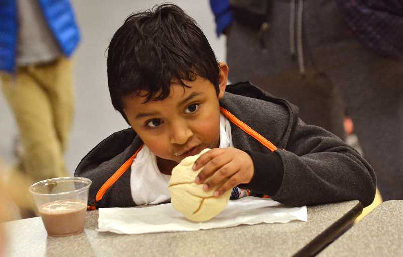SPOKESMAN PHOTO: VERN UYETAKE - Jehudaiel Guillen tries out some sweet bread  during the Nov. 9 Dual Language Family Evening.