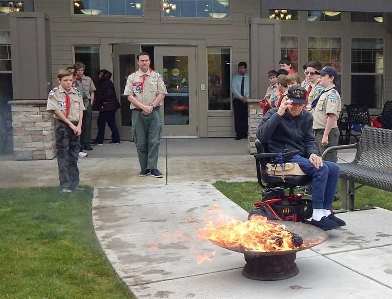 BARBARA SHERMAN - WWII Navy veteran Art Rollin salutes an American flag one last time after he placed part of it into flames in a ceremony that retired flags held at Bonaventure in Tigard on Veterans Day.