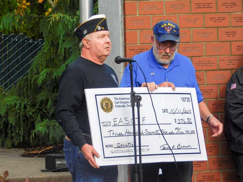 ESTACADA NEWS PHOTO: EMILY LINDSTRAND - Terry Brown of the American Legion Carl Douglas Post presents Dennis Dahrens of the Estacada Area Support Our Troops Foundation with a check during the Estacada Veterans Day celebration.