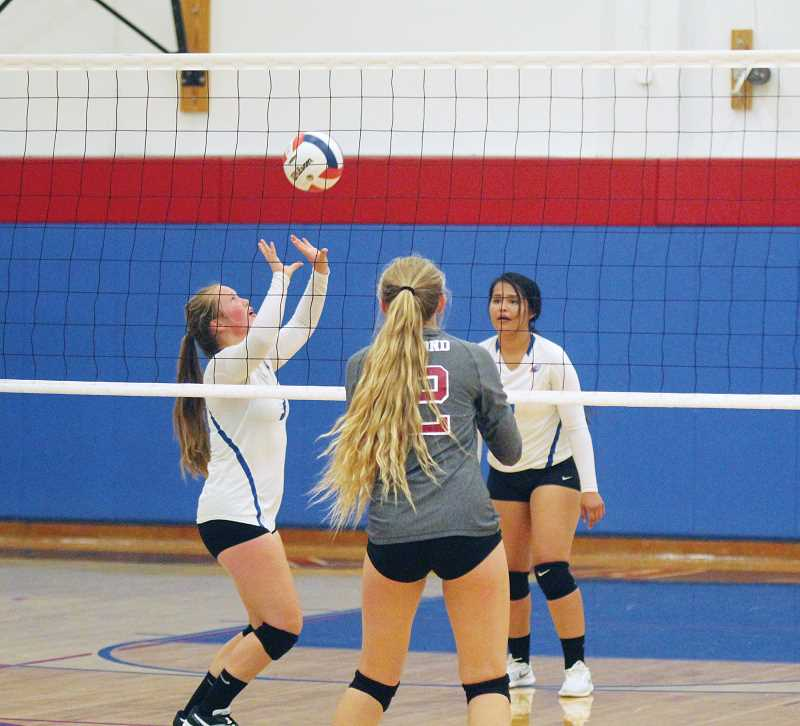 WILL DENNER/MADRAS PIONEER - Hannah Holliday (left) sets up Kiersten Anderson (right) for a hit in a home game against Redmond Aug. 31.