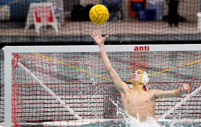 SETH GORDON - Junior goalie Wilson Johnson deflects a ball over the cage Saturday during Newberg's 9-7 win over Lakeridge in the 6A boys water polo state championship game at the Osborn Aquatic Center in Corvallis. Johnson made 17 saves in the victory and was named the all-tournament first-team goalie and overall tournament MVP.