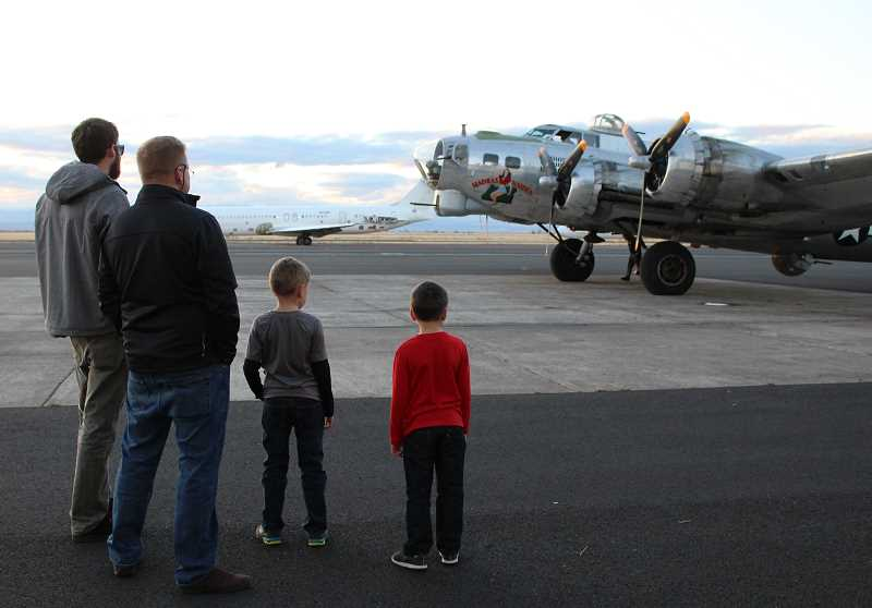 HOLLY M. GILL - Dave Reed, Jim Martinelli, and Martinelli's sons, Giovanni, 8, and Salvatore, 6, wait for the Madras Maiden's pilot and crew to disembark on Sunday afternoon, when the B-17 returned from a nine-month tour with the Liberty Foundation.