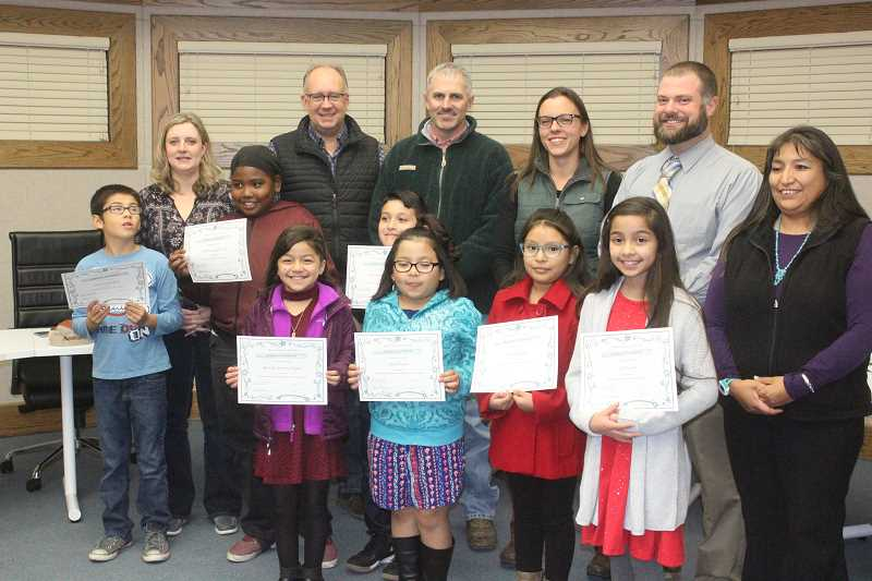 SUSAN MATHENY/MADRAS PIONEER - Metolius Elementary fourth-graders receiving awards at Monday night's school board meeting included, from left, Orren Heckathorn, Matthew Suppah Scott, Orion Reynoso Canales, Marvella Terrazas Orquiz, Ana Oliveres, Alicia Quinto and Ava Leach. School board members, from back left, are Courtney Snead, Stan Sullivan, Tom Norton Jr., Jamie Hurd, Metolius Principal Adam Dietrich, and board chairman Laurie Danzuka.