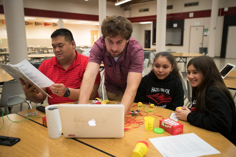 TIMES PHOTO: JAIME VALDEZ - Allen Song, left, and Daniel Bachhuber help sixth-graders Penelope Mandujano and Julie Halstad with a project at Hazelbrook Middle School. Song and Bachhuber, who are members of Tualatin Chamber of Commerce, volunteered for the after-school program.