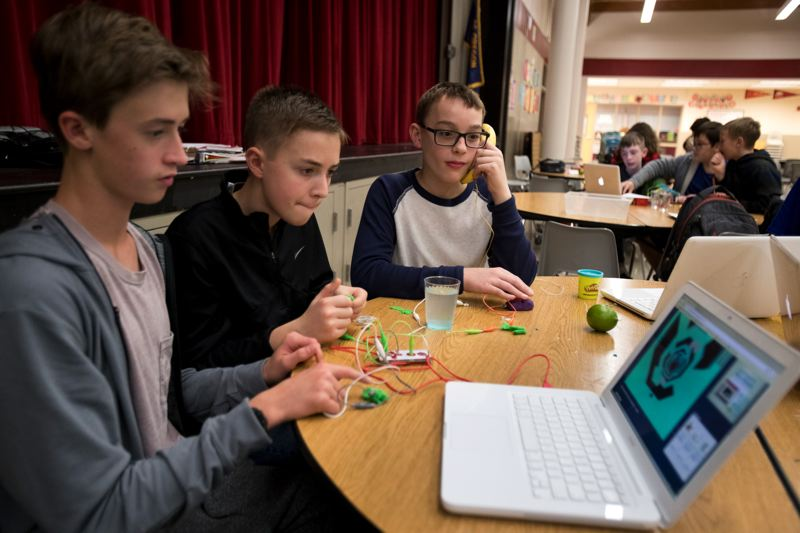 TIMES PHOTO: JAIME VALDEZ - Eighth-graders Sam Roach, Ben Unis and Joe Leonard ground their bodies to complete a circuit during a STEAM program at Hazelbrook Middle School.