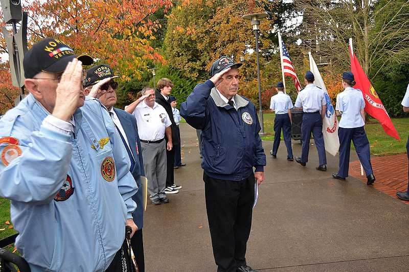 SPOKESMAN PHOTO: VERN UYETAKE - Veterans salute as the colors are retired.