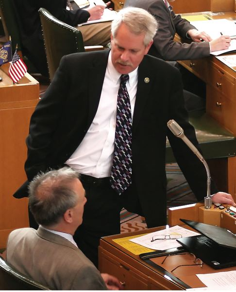 FILE PHOTO - Mark Johnson conferring with a colleague on the House floor.
