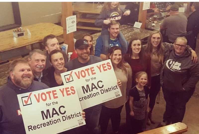 SUBMITTED PHOTO - Madras Aquatic Center Recreation District board members, employees and supporters celebrate the approval of a five-year levy renewal on Nov. 7. Executive Director Joe McHaney is holding the sign, at center.