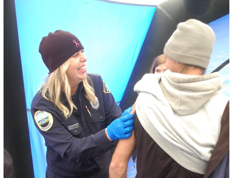 PMG FILE PHOTO: RAYMOND RENDLEMAN - Clackamas Fire Community Paramedic Amy Jo Cook applies a bandage to Daniel Knight's arm after giving him a flu shot during Resource Fair in 2017.
