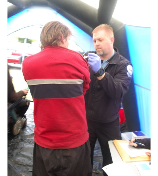 PHOTO BY RAYMOND RENDLEMAN - Community Paramedic Dan Hall of American Medical Response give a homeless person a flu shot at the Resource Fair.