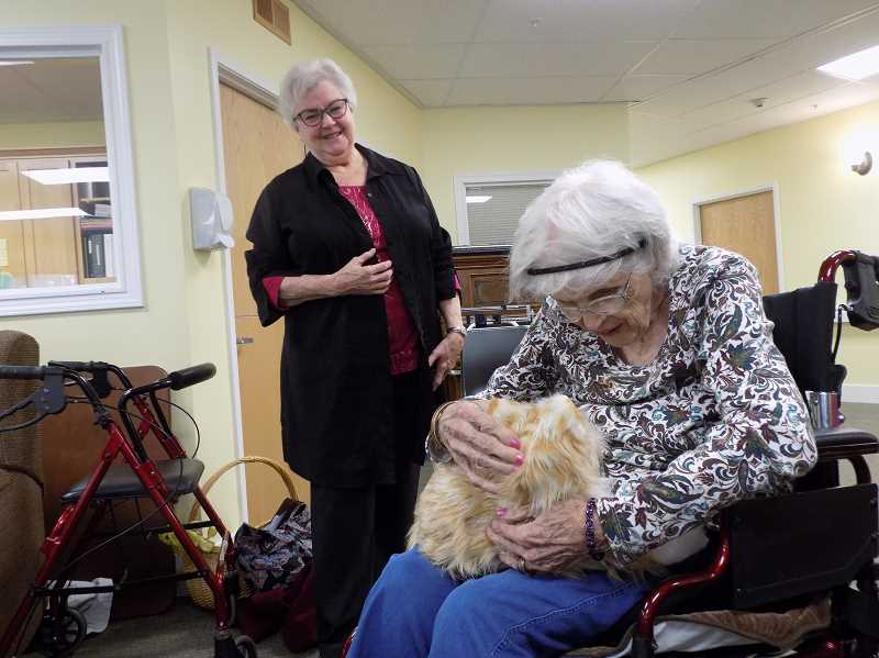 GAZETTE PHOTO: RAY PITZ - Julie Nader looks on as a resident at the Marjorie House gets a close-up look at Cuddles the robotic cat.