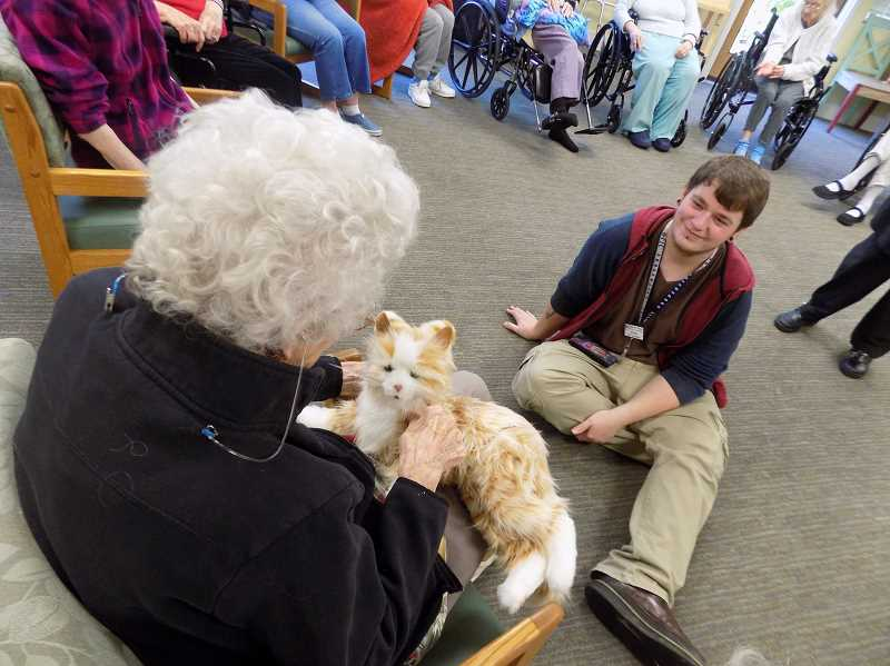 GAZETTE PHOTO: RAY PITZ - Grace Derschmidt, a resident at the Marjorie House pets Cuddles, a robotic cat, as Jordan Hunter, a life enrichment assistant at the memory care facility, looks on.