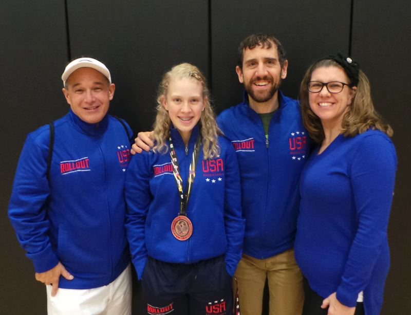 CONTRIBUTED PHOTO - Annie Roberts poses with her bronze medal from last weeks Junior World Racquetball Championships in Minneapolis along with coach Brian Ancheta, left, and parents Bryan and Danielle.