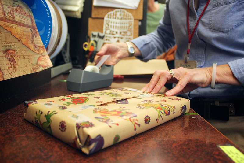 CONNECTION FILE PHOTO: KELSEY O'HALLORAN - Karen Wutzke wraps a customer's gift at Annie Bloom's Books in Multnomah Village.