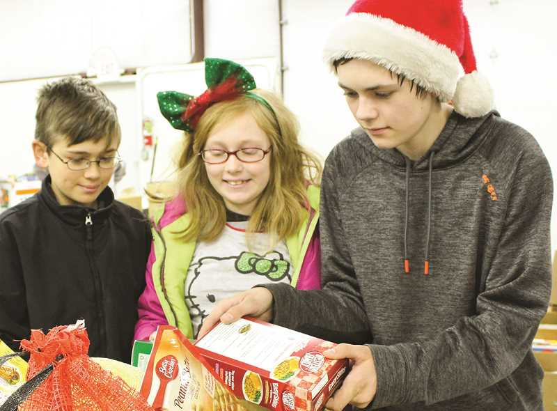 CENTRAL OREGONIAN - Left to right, Hayden, Hailey and Hunter Benson helped hand out food during distribution day last year.