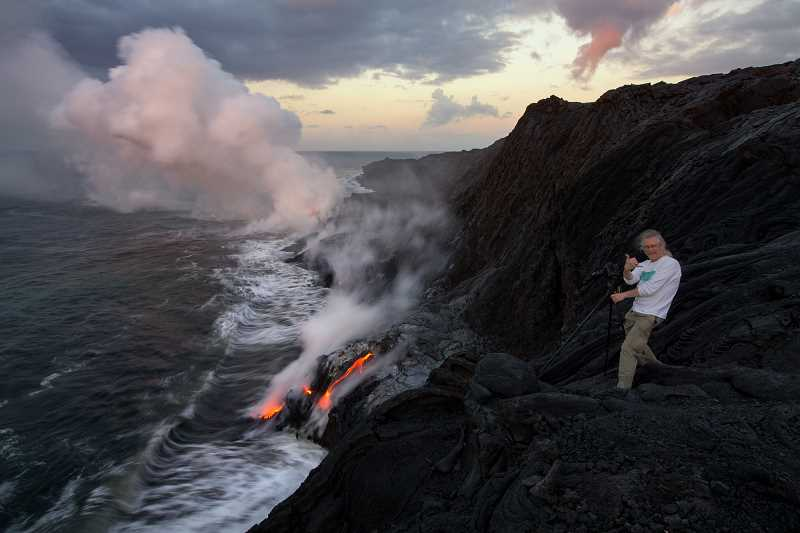 CONTRIBUTED PHOTO: BRUCE OMORI - Gary Randall eagerly takes a photo of lava in Hawaii. Randall enjoys landscape photography.
