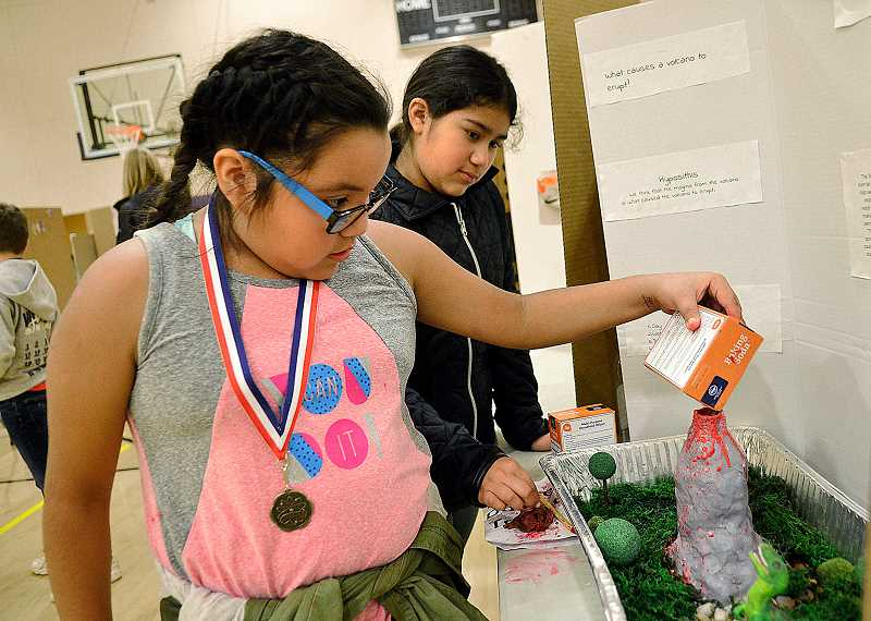 VERN UYETAKE - Fifth-graders Brittany Valdovinos, left, and Shasta Polanco demonstrate their vocano.