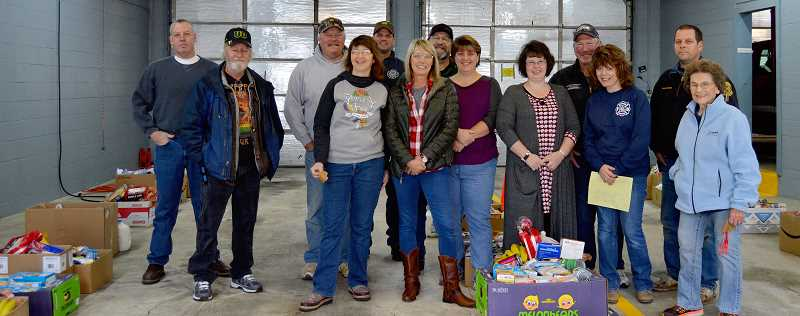 PIONEER PHOTO: CINDY FAMA - Colton Aid Network volunteers pose for a photo after finishing packing the Thanksgiving boxes. Pictured from left to right are Kyle Powell, Ron Allen, Carl Stephens, Kelly Stephens, Dan Dunn, Tara Graves, John Graves, Sherry Allen, Michele Chapman, Ron Norton, Geri Fraijo, Frank Kaneaster and Ruth Nimrod.