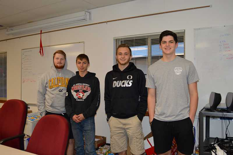 PIONEER PHOTO: CINDY FAMA - Colton High School seniors Seth Bruesch, Logan Sprague, Kris Bjorn and Kreygan Raasch moved the boxes filled with food donations from the high school to the fire department.
