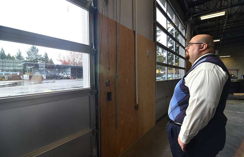 REVIEW PHOTO: VERN UYETAKE - Public Works Director Anthony Hooper stands in the Operations and Maintenance Center's new vehicle bay, looking out at the motor pool parking lot where the old Operations Center once stood. A new wash station can be seen at the other end of the lot.