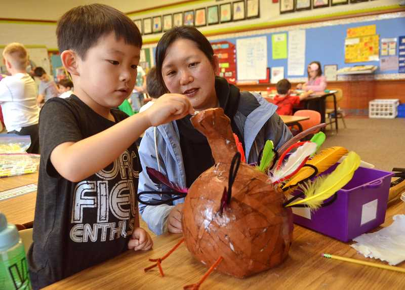 REVIEW PHOTO: VERN UYETAKE - First-grader Lucas Lee and his mom Ginny work on their turkey during pre-Thanksgiving activities last week at Forest Hills Elementary School. This week, families all across Lake Oswego are sitting down to holiday meals and giving thanks for the blessings of the season.