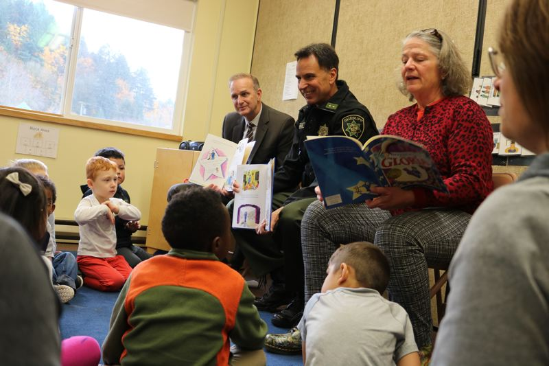 OUTLOOK PHOTO: ZANE SPARLING - From left, District Attorney Rod Underhill, Sheriff Mike Reese and Rep. Carla Piluso read from picture book 'Officer Buckle and Gloria' at a Head Start classroom on Friday, Nov. 17.