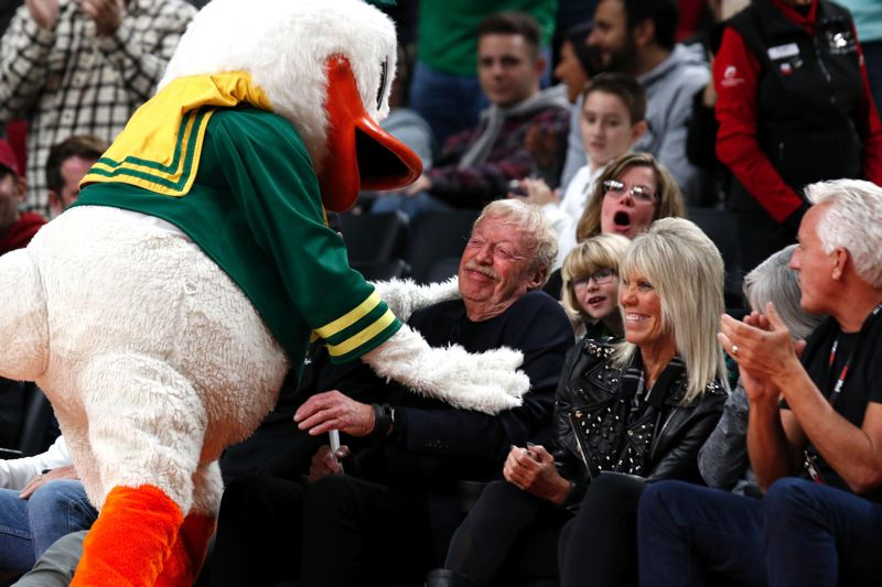 TRIBUNE PHOTO: JONATHAN HOUSE - The Duck hugs Phil Knight at Moda Center on Thanksgiving night as he watches Oregon play Connecticut in the PK80 Invitational.