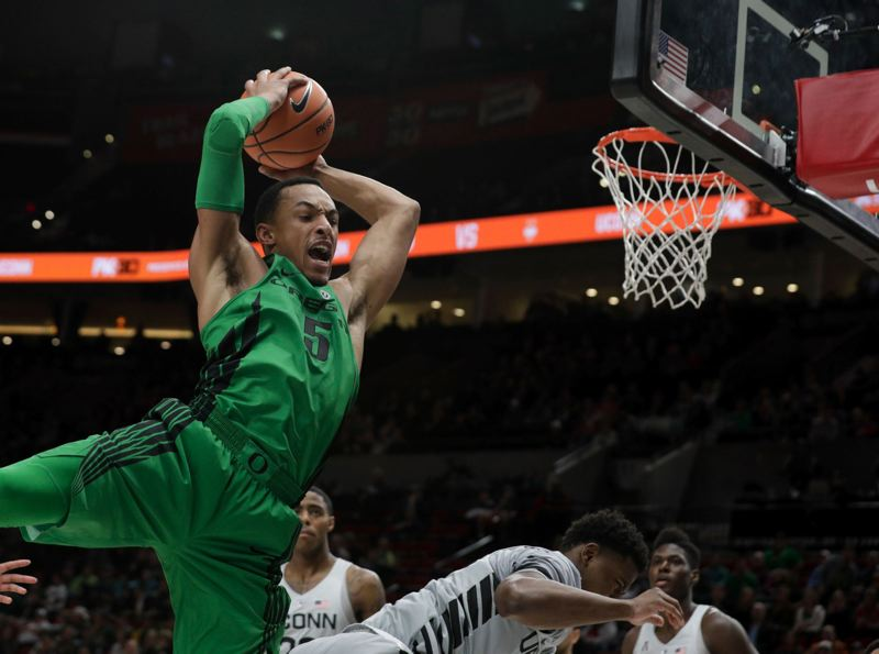 TRIBUNE PHOTO: JONATHAN HOUSE - Elijah Brown of the Oregon Ducks goes flying during a Thanksgiving night PK80 Invitational basketball game against Connecticut at Moda Center.