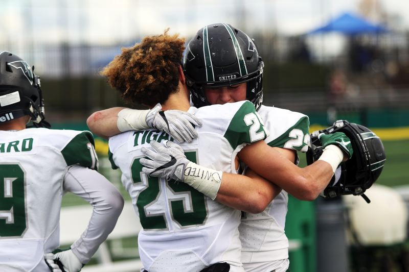 DAN BROOD - Tigard senior Braden Lenzy (25) hugs senior Jake Leavitt following the Tigers' loss to Clackamas in the Class 6A state playoff semifinals on Friday.