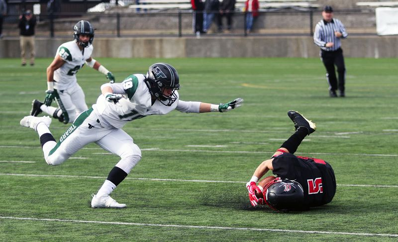 DAN BROOD - Tigard senior Skylar Holloway (left) goes after Clackamas junior Thoams Tolonen on a pass play in Friday's semifinal game.