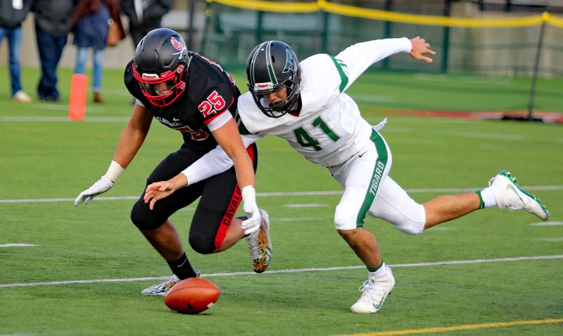 REVIEW PHOTO: JIM BESEDA - Clackamas' Justice Pagan (left) and Tigard's Drew Carter chase a fumble during the Cavaliers' 52-7 win in the Class 6A state semifinals on Friday at Hillsboro Stadium.