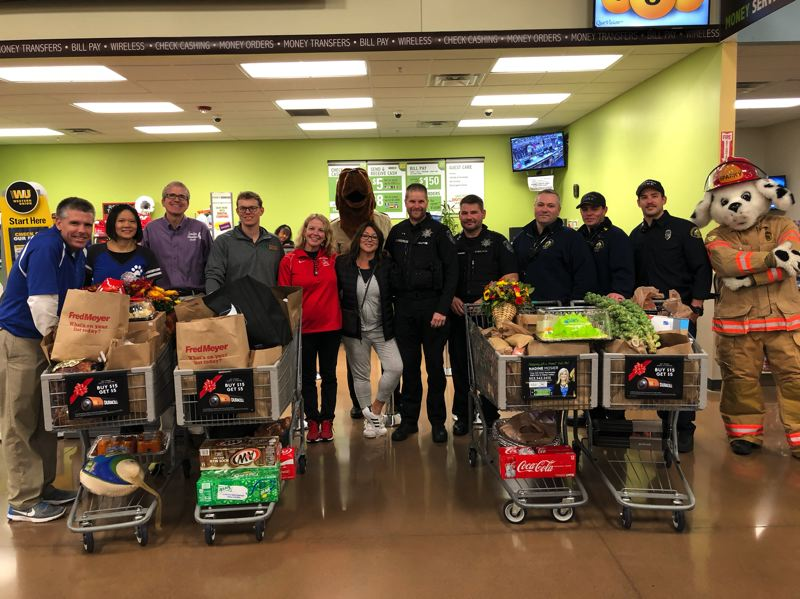 PHOTO COURTESY: STEVE CAMPBELL - North Clackamas principals and first responders from Clackamas Fire and Happy Valley police show off their carts on Nov. 16. The carts went up for auction later that day.