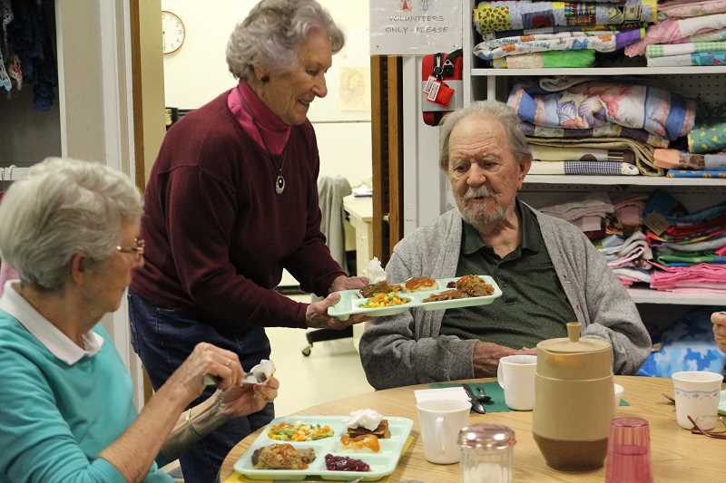 LINDSAY KEEFER - Rosemary Smith (center), a longtime volunteer with Meals on Wheels, serves lunch to seniors at the Mount Angel Community Center.