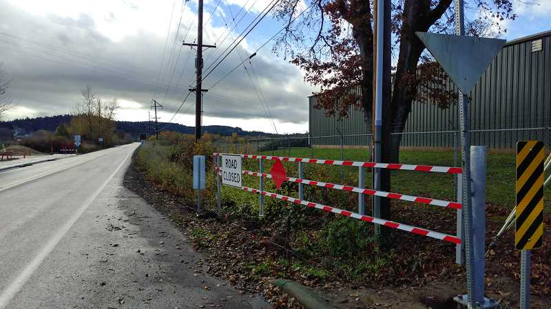 NEWS-TIMES PHOTO: STEPHANIE HAUGEN - After years of ignorant or daring drivers getting swamped on a flooded Fern Hill Road after driving around the barriers, this gate (and another on the other side of the frequently flooded stretch) will make it impossible for drivers to enter the deep water.