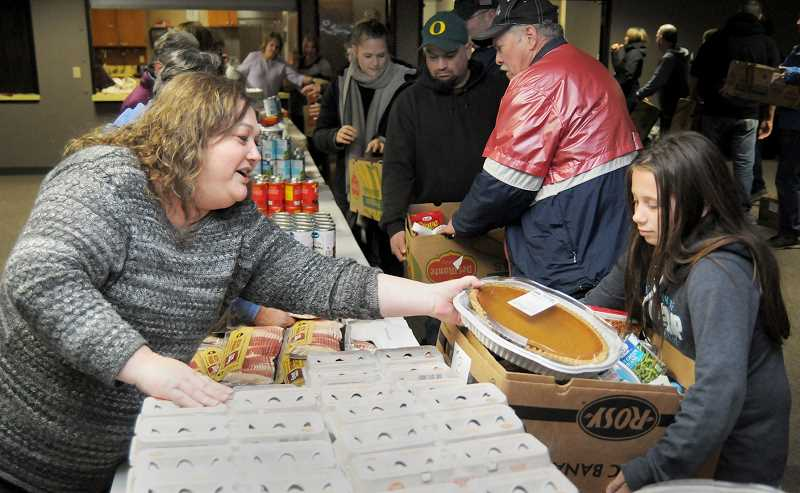 SETH GORDON - Volunteer Sherri Moore distribute a box with all the fixings for a Thanksgiving dinner to Grace Sedivec on Nov. 22 at Northside Community Church. This year, the church effort distributed 60 of its 'Thanksgiving Boxes' to those in need.