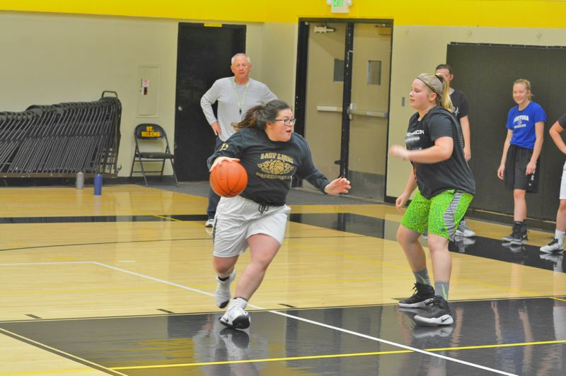 SPOTLIGHT PHOTO: JAKE MCNEAL - Madi Flores, center, attacks the basket against McKayla Foster, right, in practice Tuesday, Nov. 21, at St. Helens High School.