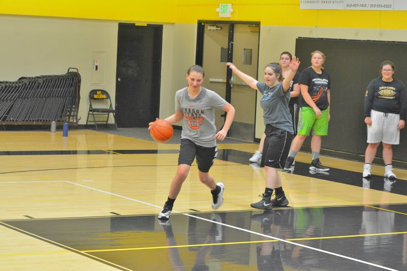 SPOTLIGHT PHOTO: JAKE MCNEAL - Madison Blazek, left, and Tayvin Degraffenreid, right, square off beneath the basket.