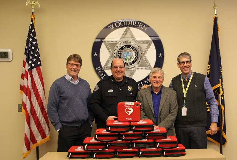 LINDSAY KEEFER - (From left) Woodburn Independent Publisher Al Herriges, Woodburn Police Chief Jim Ferraris, Woodburn Proud President Eric Swenson and Woodburn City Administrator Scott Derickson stand with 15 AEDs purchased with community-donated money.