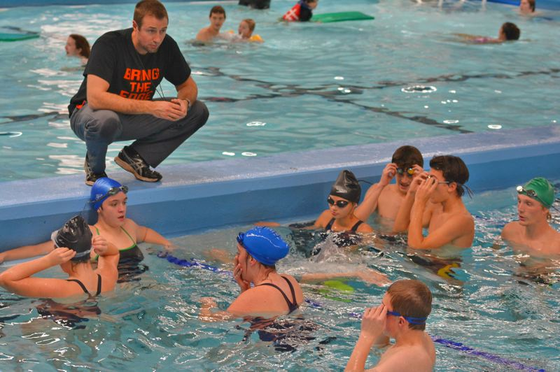 SPOTLIGHT PHOTO: JAKE MCNEAL - Indians coach David Richmond, top, confers with Emma Styles, in a blue swim cap against the wall, Lauren Herscovitz, in a black cap, Rylan Warner and Nicky Gill, in a green cap, in practice Tuesday, Nov. 21, at Eisenschmidt Pool in St. Helens.