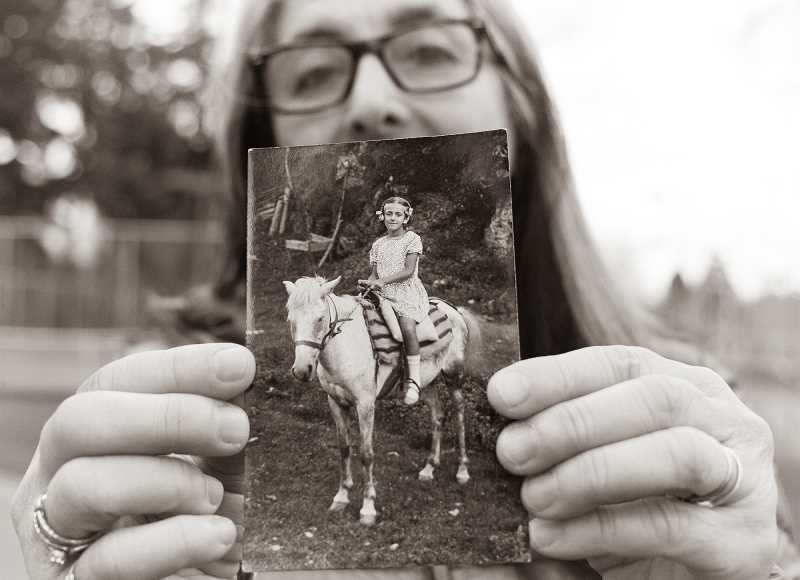 "COURTESY: IRINA BOBOIA - Stefana Berceanu, a Romanian immigrant living in the Portland area, holds up a photograph of her mother as a child. Berceanu is one of the subjects of Irina Boboia's multimedia art project, titled ""Two Worlds and Nowhere."""