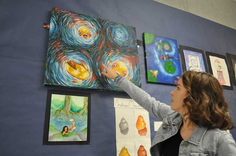 TIMES PHOTO: BLAIR STENVICK - Shelby Hansen points out her use of color and brush strokes in a painting of koi fish.