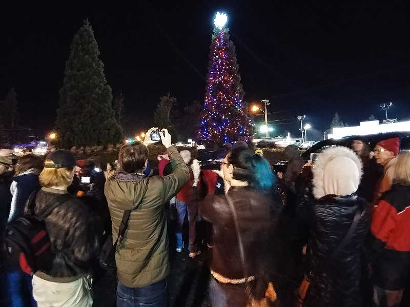 NEWS-TIMES PHOTO: CHRISTOPHER OERTELL - A crowd gathers Friday, Nov. 24, for the lighting of Forest Groves new, temporary holiday tree at Pacific Avenue and Yew Street.